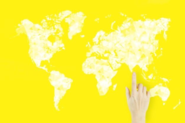Connexion de carte du monde en main. concept de connexion globale. doigt de la main de la jeune femme pointant avec hologramme sur fond jaune.