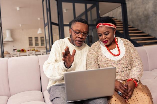Connexion internet. afro-américains positifs faisant un appel en ligne assis à la maison