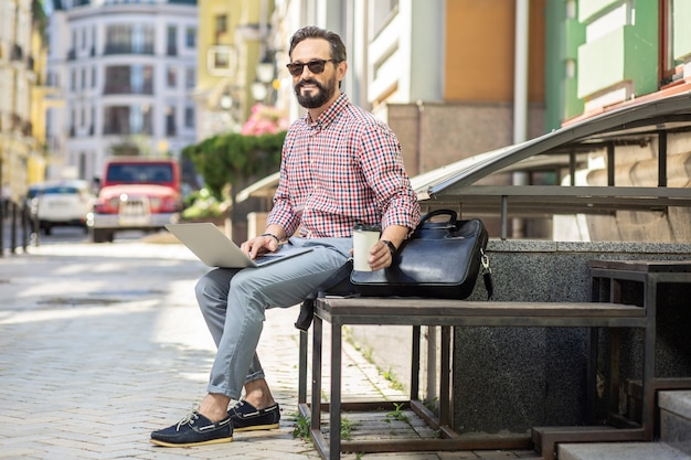 Connexion personnelle. enthousiaste pigiste masculin utilisant un ordinateur portable tout en buvant du café à l'extérieur