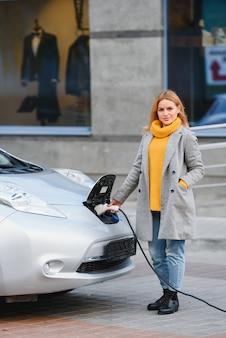 Connexion de la prise du chargeur d'une voiture électrique. la fille se tient près de sa voiture électrique et attend que le véhicule se recharge.