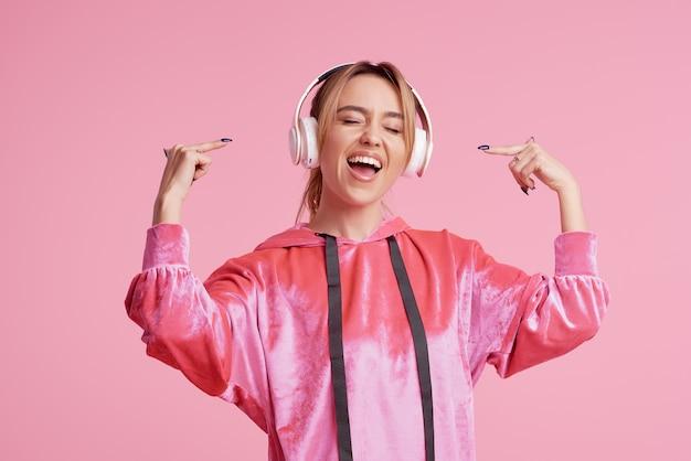 Connexion sans fil. portrait de jeune femme posant isolé sur une musique amusante d'écoute rose avec un casque.