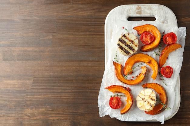 Conseil avec citrouille au four et épices sur fond en bois.