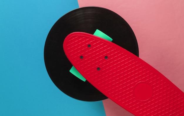 Conseil de croiseur rouge sur disque vinyle. fond bleu rose. concept de style rétro de la jeunesse. années 80. vue de dessus