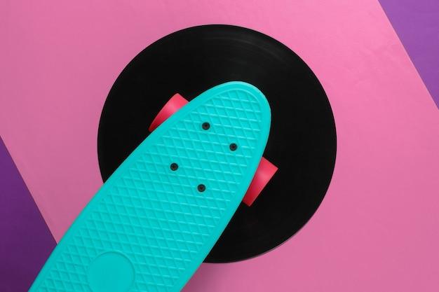 Conseil cruiser sur disque vinyle. fond rose violet. concept de style rétro de la jeunesse. années 80. vue de dessus