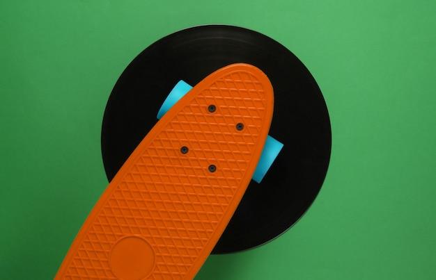 Conseil cruiser sur disque vinyle. fond vert. concept de style rétro de la jeunesse. années 80. vue de dessus