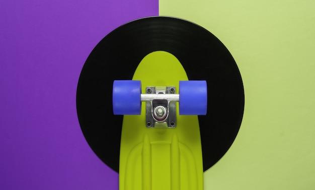 Conseil cruiser sur disque vinyle. fond vert violet. concept de style rétro de la jeunesse. années 80. vue de dessus
