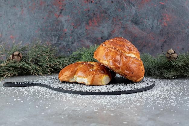 Conseil avec deux petits pains à côté de branches de pin sur une surface en marbre