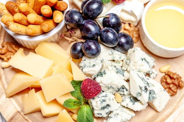 Conseil avec différents types de fromage. ensemble de mélange de fromage dor blu chedar parmesan brie sauce au miel et pain de raisin sur la palette en bois. assiette de petit-déjeuner au menu du restaurant. assortiment de collations saines.