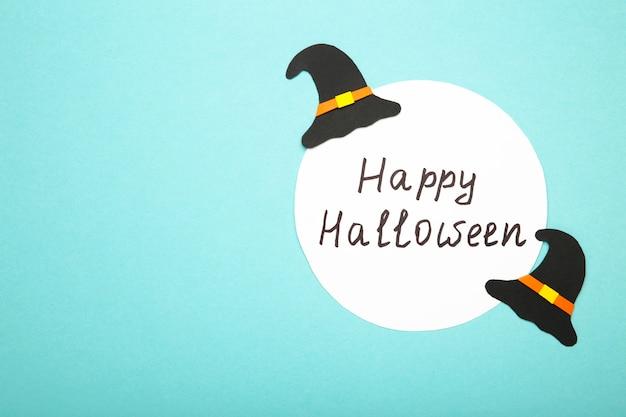 Conseil d'halloween heureux avec des chapeaux de sorcière sur une surface bleue
