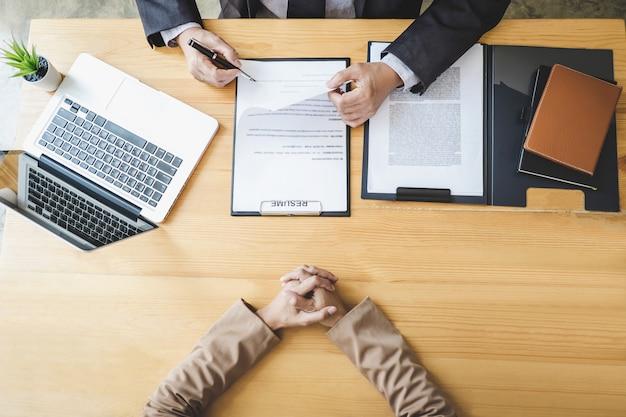 Conseil lisant un curriculum vitae pendant un entretien d'embauche, un employeur interroge une jeune chercheuse d'emploi