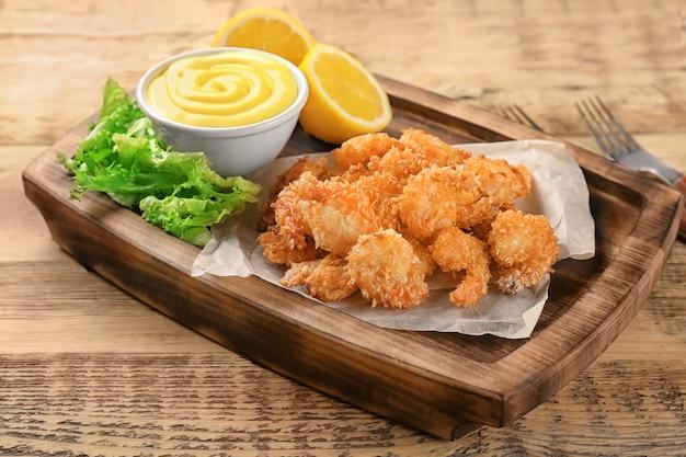 Conseil avec panier de crevettes savoureux sur table en bois