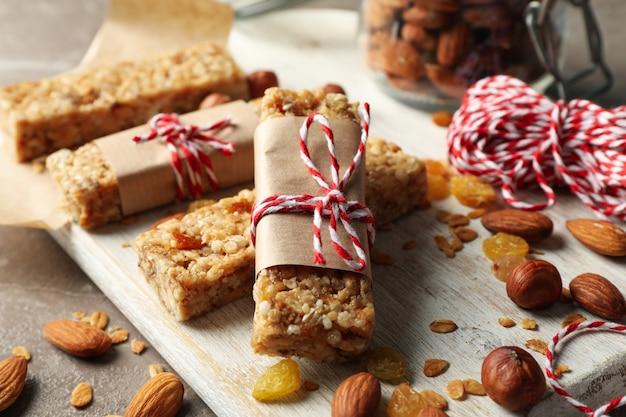 Conseil avec de savoureuses barres granola et noix sur fond gris, close up