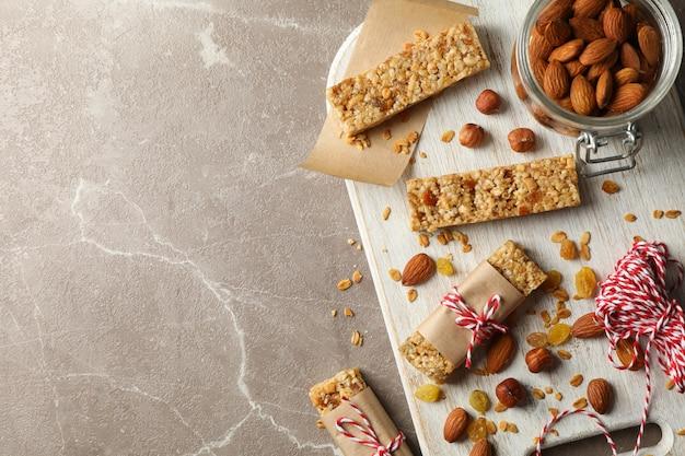 Conseil avec de savoureuses barres granola et noix sur fond gris, vue du dessus