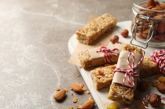 Conseil avec de savoureuses barres granola et noix sur fond gris