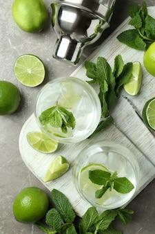 Conseil avec des verres de cocktail mojito et ingrédients sur table texturée gris
