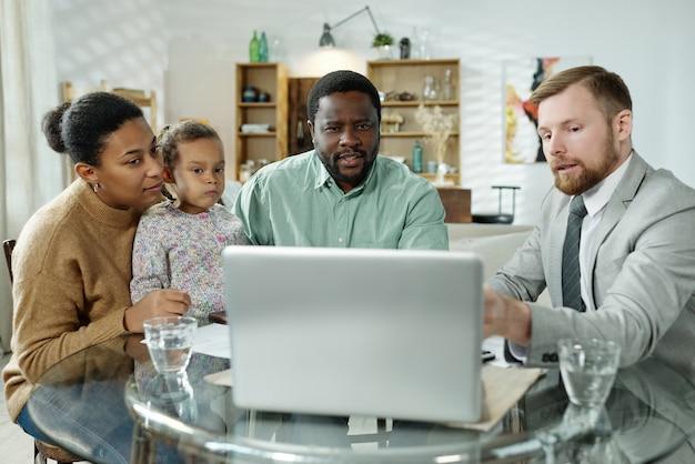 Conseiller élégant barbu montrant des informations à la famille ethnique tout en donnant une consultation de prêt immobilier