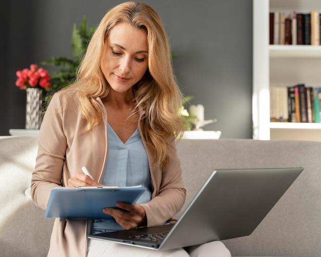 Conseiller de femme coup milieu prenant des notes avec un ordinateur portable sur les genoux