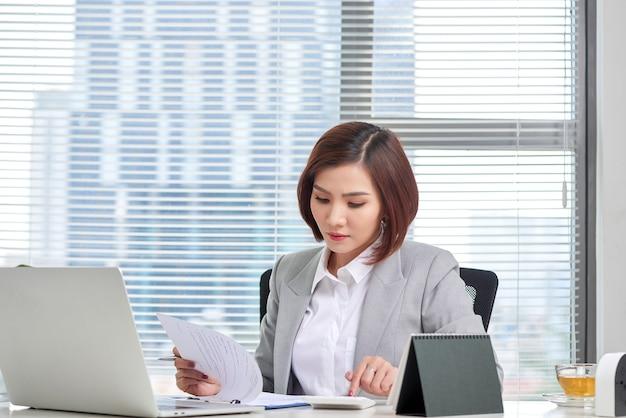Le conseiller financier à l'aide de la calculatrice examine les états financiers sur le bureau. concept de comptabilité.