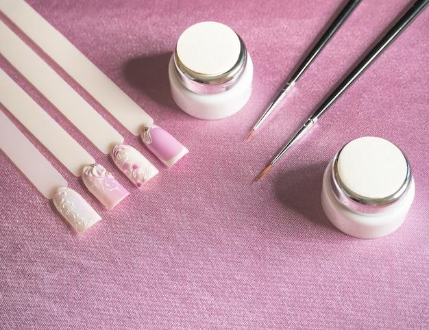 Conseils et peinture pour dessiner sur les ongles sur fond rose. concept de manucure créative.