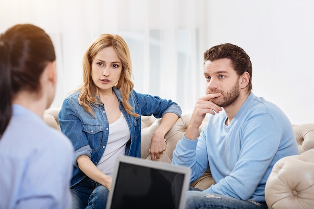 Conseils psychologiques. beau couple agréable et réfléchi assis pensivement et écoutant le psychologue tout en traitant ses problèmes