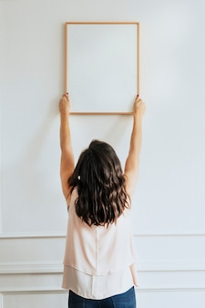 Conservateur accrochant le cadre vide sur un mur