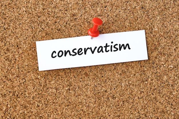 Conservatisme. mot écrit sur un morceau de papier ou une note, panneau de liège.