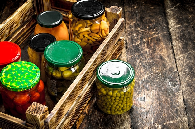 Conserve les champignons et les légumes dans une boîte. sur une table en bois.