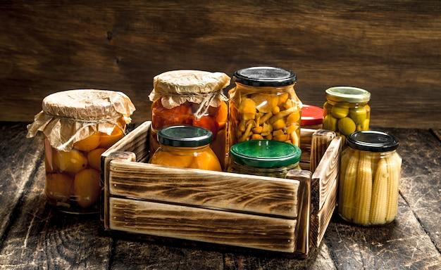 Conserve les champignons et les légumes dans une boîte sur une table en bois.