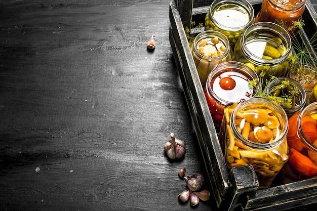 Conserve les légumes dans des bocaux en verre dans une vieille boîte. sur le tableau noir.