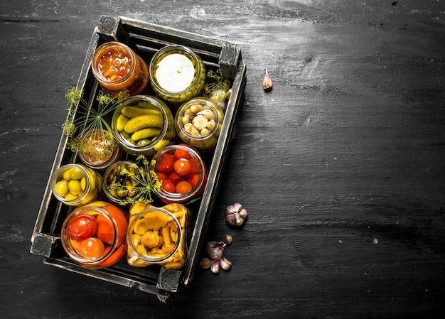 Conserve les légumes dans des bocaux en verre dans une vieille boîte.