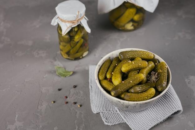 Conserver les concombres marinés, les assaisonnements et l'ail sur une table en béton gris. nourriture fermentée saine. maison de légumes en conserve.