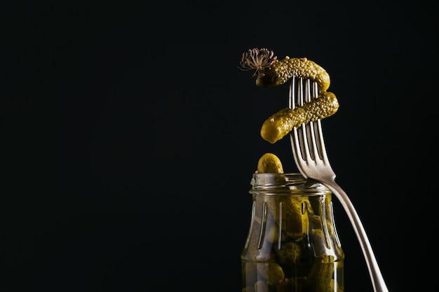 Conserver les concombres marinés, les assaisonnements et l'ail sur une table sombre. nourriture fermentée saine. maison de légumes en conserve.