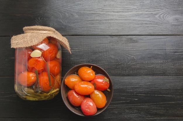Conserves de légumes tomate dans des bocaux en verre sur une planche de bois sombre. vue d'en-haut.