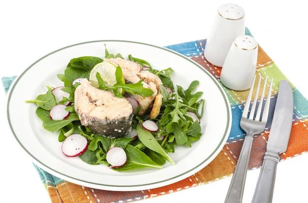 Conserves de poisson avec des verts sur plaque isolée sur blanc.