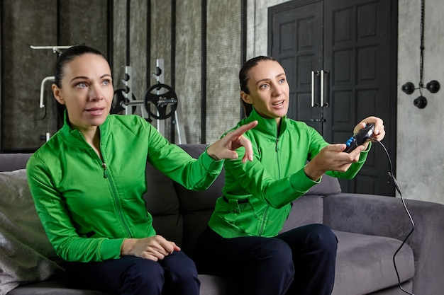 Console de jeu entre les mains d'une femme passionnée assise sur un canapé dans un loft à côté de sa sœur et