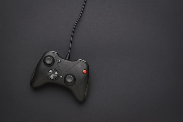 Une console de jeu noire avec un fil sur fond noir. un appareil pour jouer à des jeux informatiques. mise à plat.