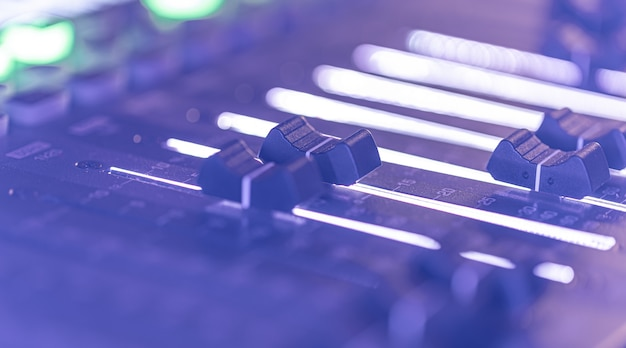 Console de mixage audio professionnelle avec faders et commandes.