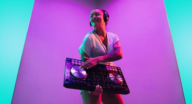 Console de mixage. jeune musicienne au casque sur fond violet à la lumière du néon. concept de musique, passe-temps, festival, divertissement, émotions. hôte joyeux, dj, portrait d'artiste