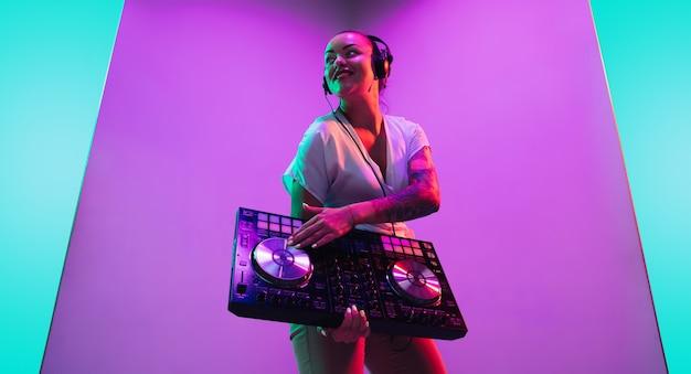 Console de mixage jeune musicienne au casque sur fond violet