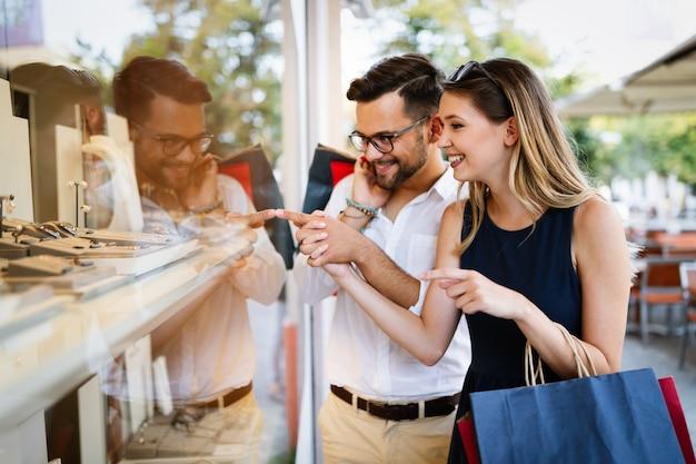 Consommation, amour, rencontres, concept de voyage. heureux couple faisant du shopping en s'amusant