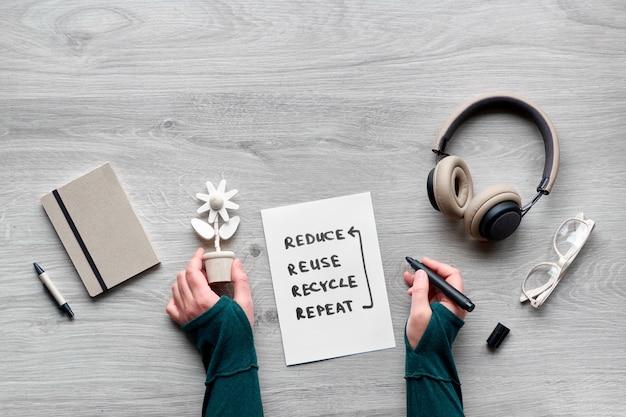 Consommation consciente à plat, vue de dessus des mains tenant une fleur en bois, ordinateur portable avec couverture en carton artisanal, lunettes de lecture et écouteurs sur table en bois. mode de vie minimal, idée zéro déchet.