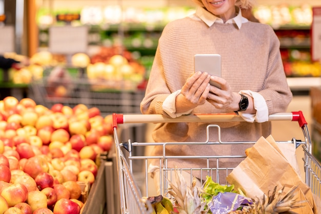 Consommatrice mature en pull beige tricoté poussant le chariot avec des produits alimentaires en supermarché et défilement dans le smartphone
