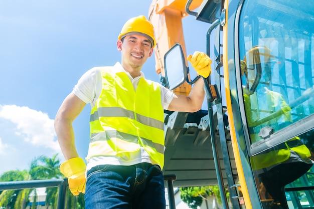 Constructeur asiatique avec excavatrice sur chantier