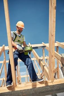 Constructeur barbu heureux gardant le sourire sur son visage tout en allant scier des planches