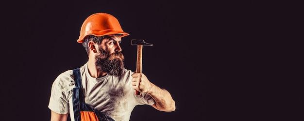 Constructeur barbu isolé sur fond noir. travailleur barbu avec barbe, casque de construction, casque.