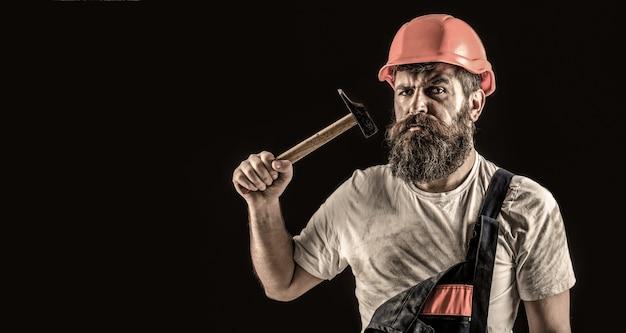 Constructeur barbu isolé sur fond noir. travailleur homme barbu avec barbe, casque de construction.