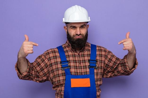 Constructeur barbu en uniforme de construction et casque de sécurité à la confiance souriante pointant sur lui-même debout sur fond violet