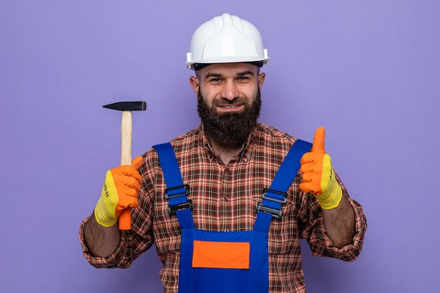 Constructeur barbu en uniforme de construction et casque de sécurité portant des gants en caoutchouc tenant un marteau à sourire confiant montrant les pouces vers le haut