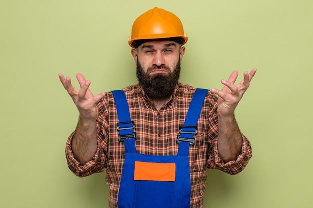 Constructeur barbu en uniforme de construction et casque de sécurité regardant la caméra confus haussant les épaules debout sur fond vert