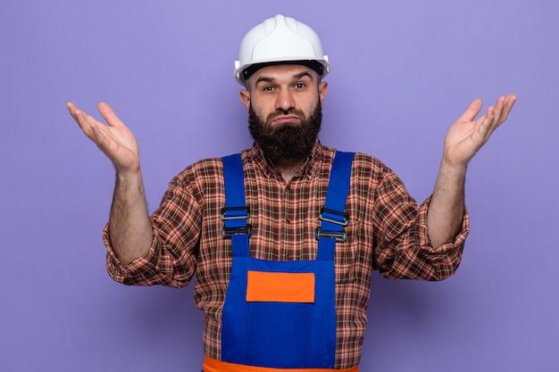 Constructeur barbu en uniforme de construction et casque de sécurité regardant canera confus levant les bras n'ayant pas de réponse